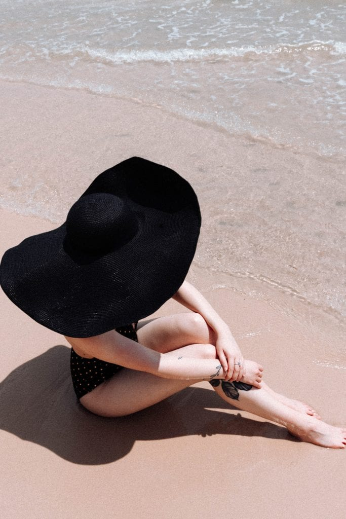Girl sat in beach with big hat