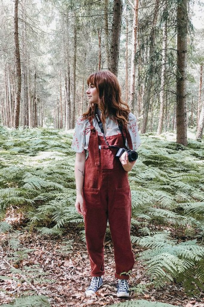 girl in woods holding camera